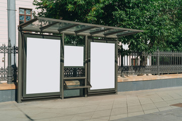 Two vertical blank white billboards at bus stop on city street. In the background buildings and trees. Mock up. Poster on street next to roadway. Sunny summer day.