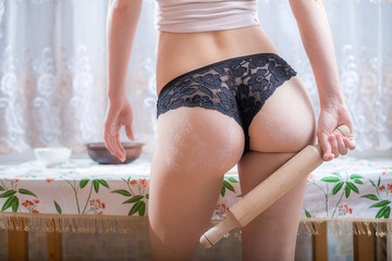 Sexy young woman wearing lacy panties in the kitchen.