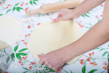 Female hands rolling out dough for homemade baking.