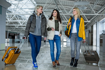 Recreation concept. Full length of three girls with baggage walking through airport and communicating
