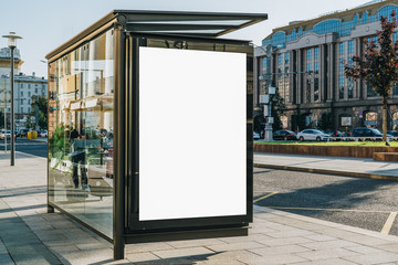 Vertical blank white billboard at bus stop on city street. In the background buildings and road. Mock up. Poster on street next to roadway. Sunny summer day. Fototapete