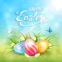 Blue sunny background with Easter eggs in grass
