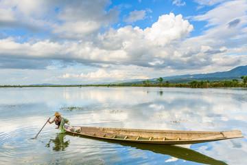 Myanmar, Lac Inle: Un pêcheur sur sa pirogue pose ses filets.