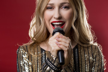 Beautiful serene lady holding speaker close to her mouth and performing a song. Isolated on red background