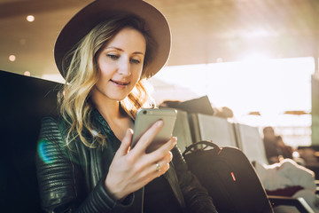 Young woman tourist in hat, with backpack sits at airport and uses smartphone. Hipster girl is waiting for plane landing, checks email, chatting, blogging, browsing internet.
