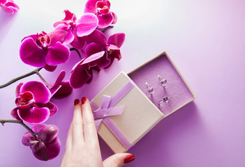 Woman opens a gift box with a set of amethyst jewellery surrounded with orchid