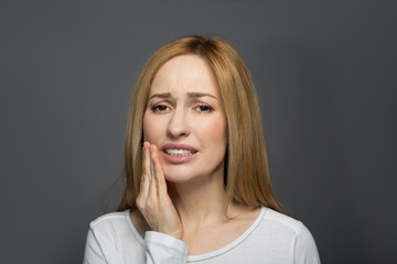 Dental treatment. Portrait of joyless female holding her hand on cheek and wincing in pain. Isolated on background