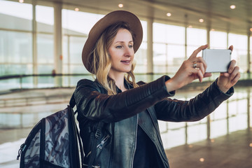 Young tourist woman in hat and with backpack stands at airport and takes photos, shoots video on smartphone's camera. Hipster girl uses digital gadget. Blurred background, bokeh effect.