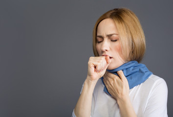 Health concept. Portrait of displeased girl in scarf holding one hand near her mouth and coughing. Copy space in left side. Isolated on background