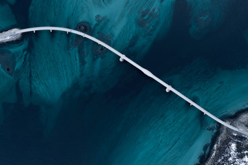 Aerial shot of a bridge over sea strait. Visible depth with blue and green colours near Tromso. Sommaroy, Norway Fotoväggar