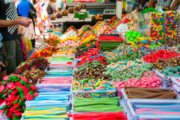 Customers choose sweets from counter with assorted colorful different shape jelly candies on market place in Tel Aviv, Israel. Selective focus, space for text.