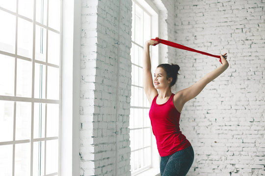 Cropped view of beautiful happy young female with flexible athletic body doing stretching exercises indoors, helping herself with red fitness strap, smiling as she enjoys such healthy activity