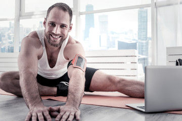 Excellent stretching. Gay positive optimistic sportsman grinning while staring at camera and putting hands on floor