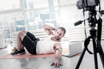 Body up. Energetic strong male blogger improving abs while lying on mat board and filming video