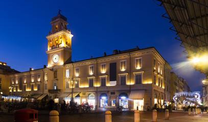 Parma city hall illuminated at dusk and monument