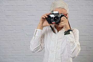 Portrait of beautiful mature woman using vintage camera. Travel, Vacation, Active senior lifestyle