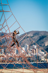 Little boy climbing on the rope at playground in Benidorm beach