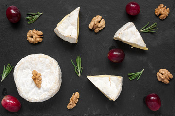 Cheese with white mold. composition of camembert or brie cheese with grapes, walnuts and of rosemary