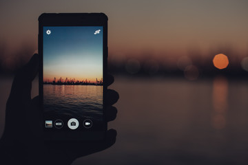 Tourist taking photo of sea harbor with mobile device at sunset