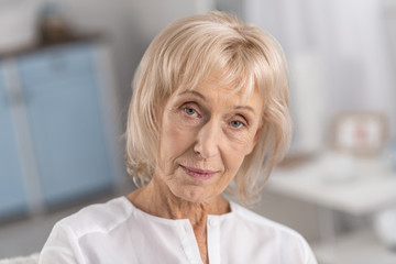 Pensive mood. Portrait of earnest pleasant mature woman looking at camera while considering and posing on the blurred background