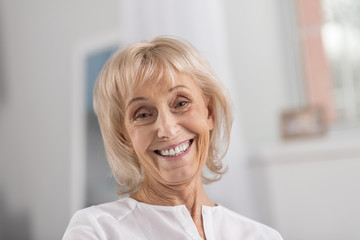 White smile. Happy merry mature woman gazing at camera while posing on the blurred background and grinning