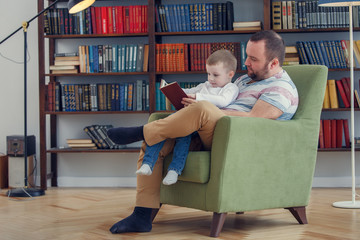 Picture of father reading book to son sitting in chair