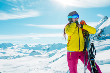 Photo of sporty woman with skis on background of snowy landscape