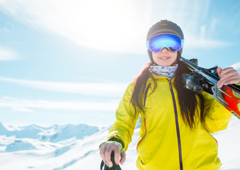 Photo of sports girl wearing helmet, a mask with skis on her shoulder