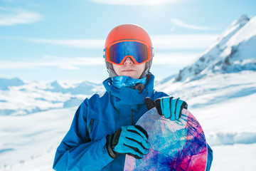 Picture of sports man in helmet looking at camera with snowboard on background of snowy hill