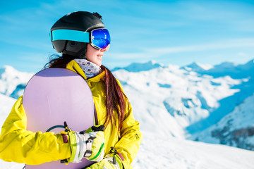 Picture of smiling woman in helmet and mask with snowboard on background of snowy hills