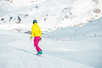 Photo from back of girl in sports clothes snowboarding