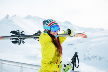 Photo of smiling sports woman with skis on her shoulder against