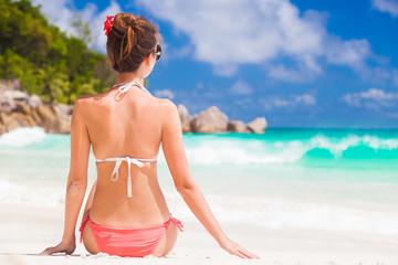 back view of long haired woman in bikini on tropical beach