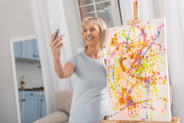 I creating this. Talented nice mature woman using phone for shooting and easel standing