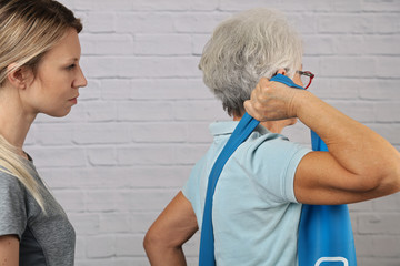 Senior woman having chiropractic back adjustment. Osteopathy, Alternative medicine, pain relief concept, Physiotherapy, injury rehabilitation treatment with Resistance Band