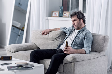 Photo sur Plexiglas Bar Doing nothing. Calm lazy alcohol addicted man sitting on a soft sofa with a bottle in his hand and watching TV while drinking beer