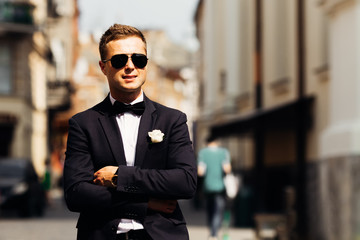 beautiful groom in a black suit and sunglasses on the background
