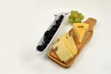Cheese with olives stock images. Cheese chopping board. Cheese with grapes isolated on a white background. Healthy snack images