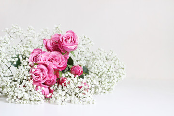 Wedding styled stock photo. Still life with pink roses and baby's breath Gypsophila flowers on white table background. Floral composition. Image for blog or social media.