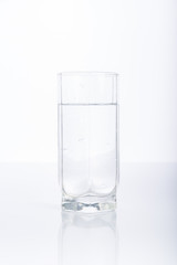 Glass of purified water on white background, reflection