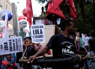"Children of a garbage recycler hold signs reading ""Election without Lula is fraud"" as they take part in a protest against Brazil's President Michel Temer's proposal to reform the social security system in Sao Paulo"