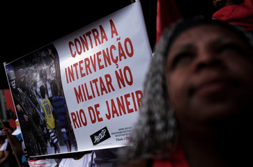 "A demonstrator holds a sign reading ""Against military intervention in Rio de Janeiro"" in a protest against Brazil's President Michel Temer's proposal to reform the social security system in Sao Paulo"