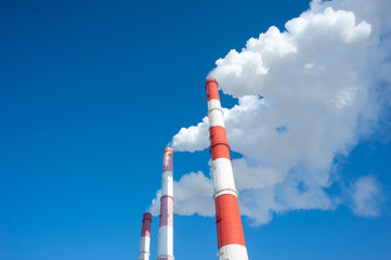 Air pollution by smoke coming from three factory chimneys