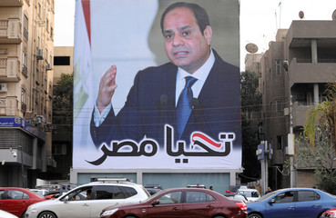 Cars pass by a poster of Egypt's President Abdel Fattah al-Sisi for the upcoming presidential election, in Cairo