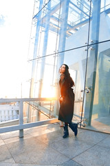 young successful beautiful girl stands on the roof of a building on a high rise background