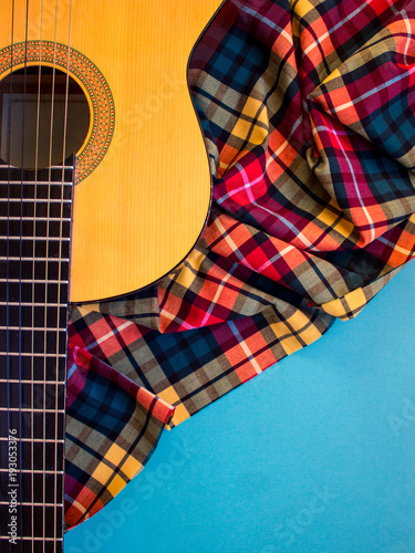 Acoustic classic guitar on plaid background  Folk country