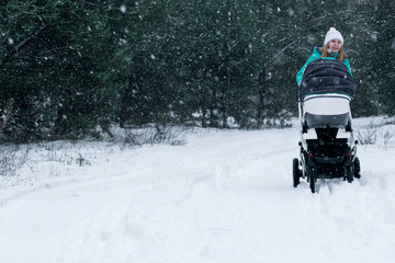 Young beautiful mother walking with stroller in city park at winter. Happy motherhood concept. Free space for text.