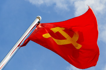 A red flag with communist symbols of a sickle with a hammer flying in a blue sky