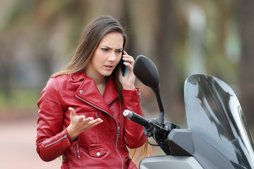 Angry motorbiker calling on phone on a motorbike