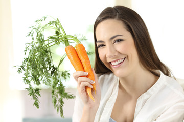 Girl showing a bundle of carrots looking at camera